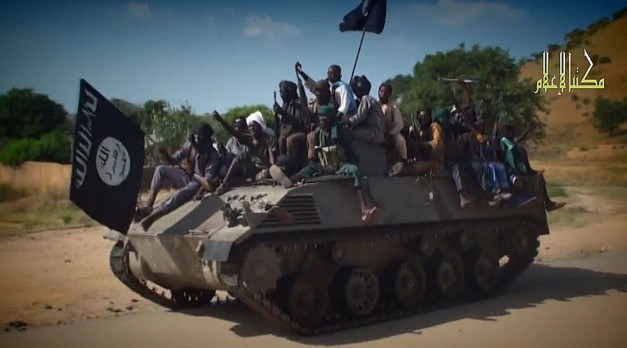 A screengrab taken on November 9, 2014 from a new Boko Haram video released by the Nigerian Islamist extremist group Boko Haram and obtained by AFP shows Boko Haram fighters parading on a tank in an unidentified town. © AFP Photo
