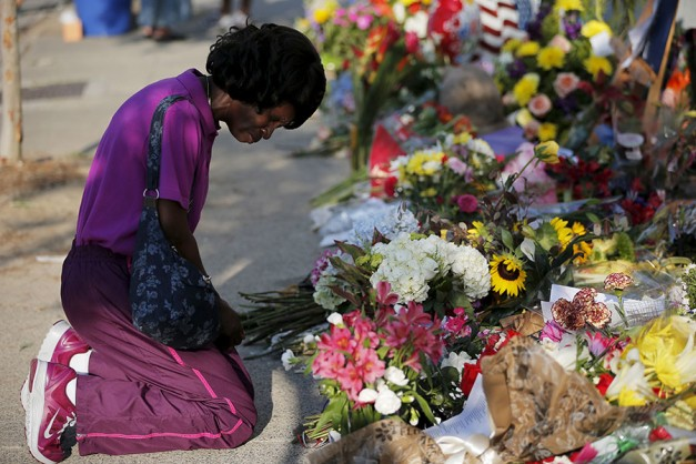 Patricia Bailey prays at a makeshift memorial outside the Emanuel African Methodist Episcopal Church in Charleston, South Carolina June 20, 2015, three days after a mass shooting which left nine people dead during a bible study at the church. ©Brian Snyder