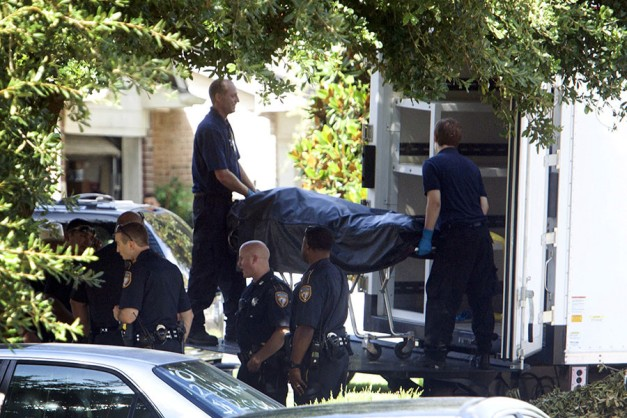 The second of eight bodies is loaded into the coroner's truck at the scene of a shooting in which eight people were killed, in Houston, Texas August 9, 2015. ©Daniel Kramer