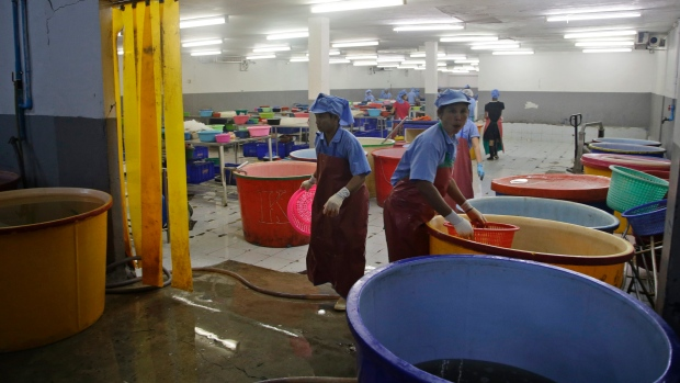 Workers at a Thai shrimp factory are shown as the facility was being raided by authorities. A major AP investigation says slave-like conditions are rampant in the industry.