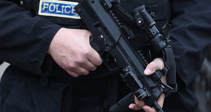 An armed police officer holds his weapon
