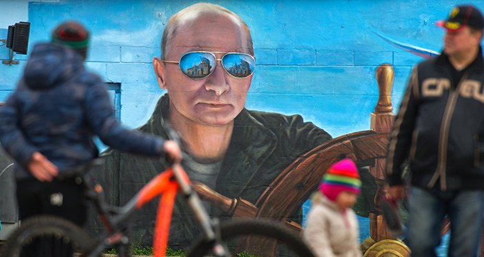 Pedestrians near a portrait of Russian President Vladimir Puitn on a wall of a building in Yalta
