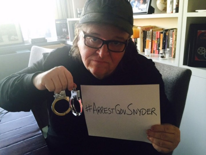 Michael Moore holds a sign calling for Flint's governor to be detained. Credit: Michael Moore