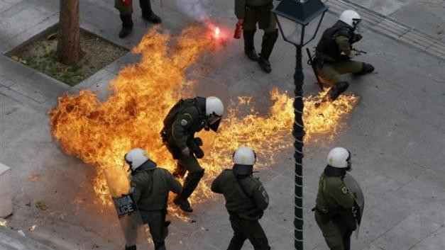 Riot policemen try to avoid a petrol bomb thrown by protesters in Athens, Feb. 4, 2016. (Photo by AP)
