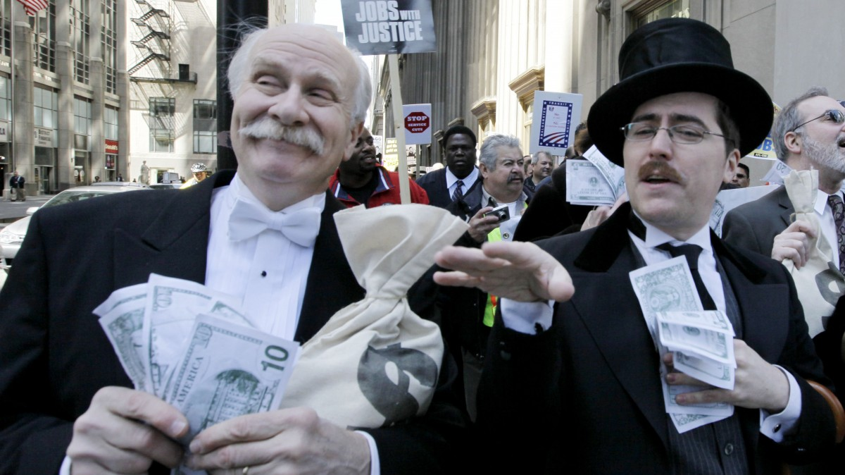 Protesters Richard Hanzel, left, Brendan Hutt, and Richard Shavzin, right, of the Screen Actors Guild, dressed as wall street bankers, march from Goldman Sachs' office to a rally in Federal Plaza demanding Wall Street reform, Wednesday, April 28, 2010, in Chicago.