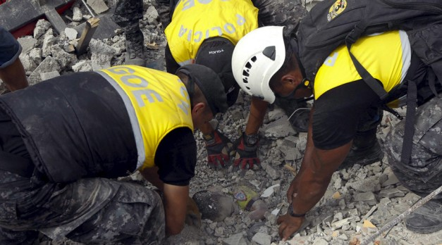 Police officers uncover the body of a victim after an earthquake struck off Ecuador's Pacific coast, at Tarqui neighborhood in Manta April 17, 2016. © Guillermo Granja