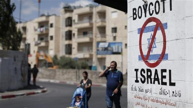 Palestinians walk past a sign painted on a wall in the occupied West Bank town of Bethlehem on June 5, 2015, calling to boycott Israeli products coming from illegal settlements. ©AFP