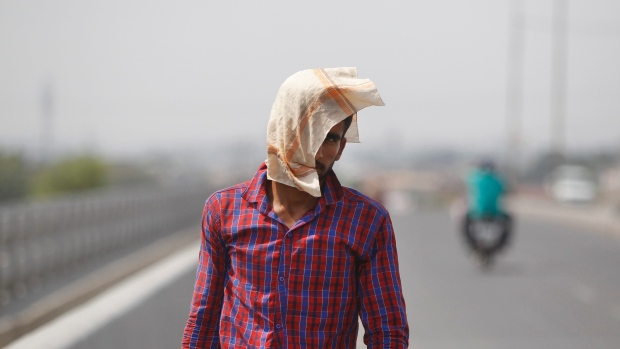A man uses a cloth to protect himself from the sun during a hot summer day in Jammu, India, Friday. The prolonged heat wave this year has already killed hundreds and destroyed crops in more than 13 states, impacting hundreds of millions of Indians.