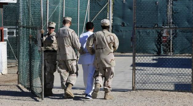 US Navy guards escort a detainee through Camp Delta at Guantanamo Bay naval base. © DoD / 1st Lt. Sarah Cleveland