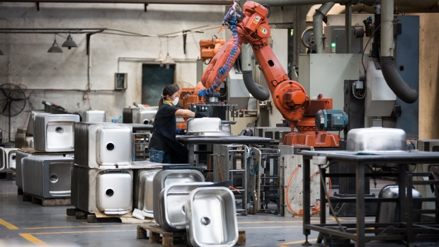 A robotic arm helps manufacture sinks at Ying Ao Kitchen Utensils in Foshan, China. The company recently replaced 256 workers with nine of the robotic machines.