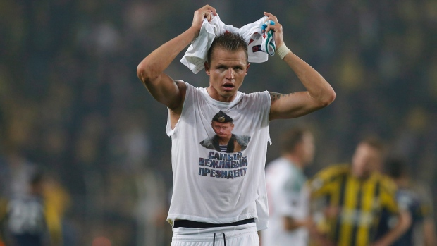 Locomotiv Moscow's Dmitri Tarasov shows off an inner shirt with a picture of Russian President Vladimir Putin and the slogan 'most polite president,' following a Europa League match against Fenerbahce in Istanbul on Feb. 16, 2016.