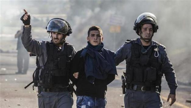 Israeli soldiers arrest a Palestinian boy in the West Bank.