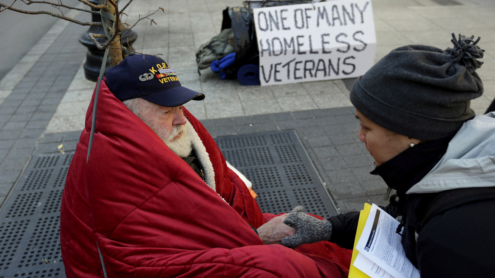 In this Wednesday, Nov. 20, 2013 photo, homeless Korean War veteran Thomas Moore, 79, left, speaks with Boston Health Care for the Homeless street team outreach coordinator Romeena Lee on a sidewalk in Boston. Moore, who said he accidentally killed his best friend with a phosphorous grenade during one firefight and spent months afterward at Walter Reed Army Medical Center in Washington, also said he has no interest in getting a government-subsidized apartment. (AP Photo/Steven Senne)