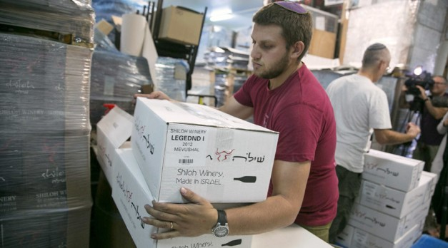 A worker carries boxes containing wine bottles for export at Shiloh Wineries, north of the West Bank city of Ramallah November 8, 2015. © Baz Ratner