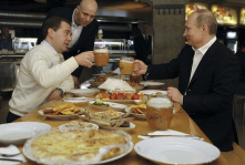 File photo of Russian President Medvedev and PM and President-elect Putin toasting with beer during a visit to a restaurant in Moscow