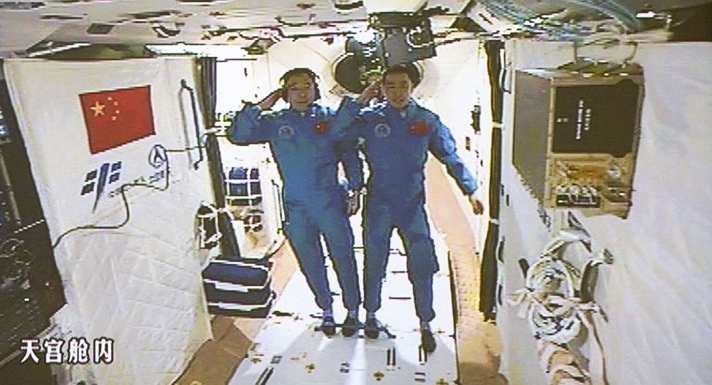 In this image taken off the screen at the Beijing Aerospace Control Center on Wednesday, Oct. 19, 2016 and released by Xinhua News Agency, two Chinese astronauts Jing Haipeng, left and Chen Dong salute in the space lab Tiangong 2