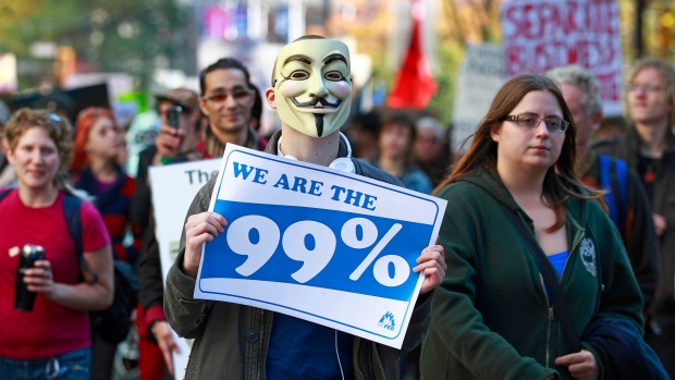 A man holds up a protest sign as he marches with thousands of people through the streets participating in the Occupy Vancouver protest on Oct.15, 2011. A new report called 'An Economy for the 99%' paints a stark picture of wealth inequality in Canada and around the world.