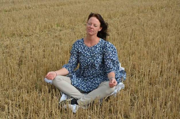 Image shows a woman meditating.