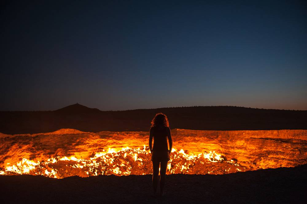 A person's silhouette in front of the top of a volcano or a giant pit of fire.