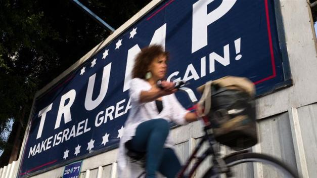 An Israeli cyclist passes a placard proclaiming 'Trump Make Israel Great Again' in Tel Aviv, Israel on November 12, 2016 [Jim Hollander/EPA] [EPA]