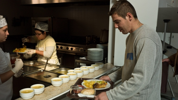 In this photo from Nov. 2010, Tiago, a patient and resident, picks up his lunch from the kitchen of a treatment centre in Lisbon, Portugal. At the treatment centre where he lives, he plays table tennis, surfs the Internet, watches TV and also helps with cleaning and other odd jobs.
