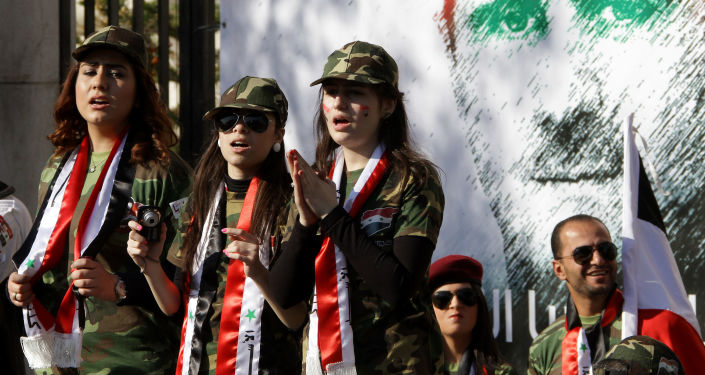 Syrian pro-regime supporters dressed in military uniform stand in front of a mural of President Bashar al-Assad during a rally in Damascus. File photo