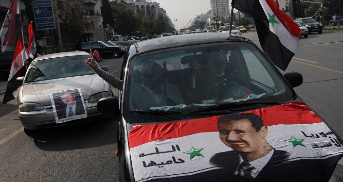 Syrians display national flags and banners with photos of Syrian President Bashar Assad during a pro-government event in Damascus, Syria. (File)