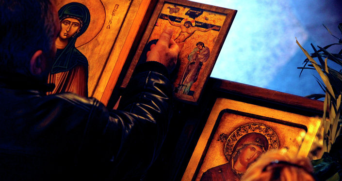 A man touches an icon with the crucifixion of Jesus Christ on Good Friday at St. Petka Orthodox church in Skopje, Macedonia