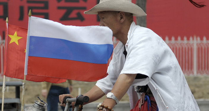 A man rides with a Russian flag displayed on his pedicab in Beijing's Russian trade district of Yabaolu. file photo
