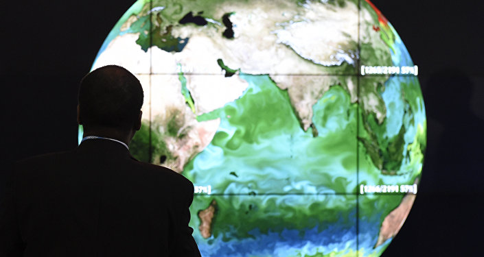 A conference attendee looks at a projection of the Earth on the opening day of the COP 21 United Nations conference on climate change, on November 30, 2015 in Le Bourget