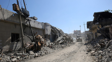 FILE PHOTO: An Iraqi forces' vehicle drives past destroyed buildings in the Mosul al-Jadida area on March 26, 2017 © Aahmad Al-Rubaye