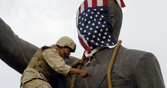A US Marine covers the head of a statue of Iraqi President Saddam Hussein with the US flag before pulling it down in Baghdad's al-Fardous (paradise) square 09 April 2003 as the marines swept into the Iraqi capital and the Iraqi leader's regime collapsed.