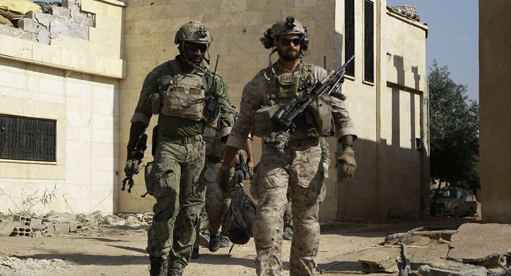 Armed men in uniform identified by Syrian Democratic forces as US special operations forces walk in the village of Fatisah in the northern Syrian province of Raqa on May 25, 2016
