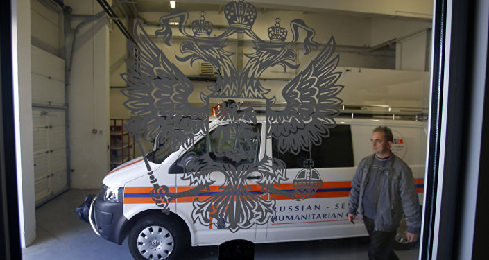 In this Thursday, Sept. 29, 2016 photo, a worker passes by a rescue mission van in a warehouse in a Russian-Serbian Humanitarian Center near an airport in the town of Nis, Serbia