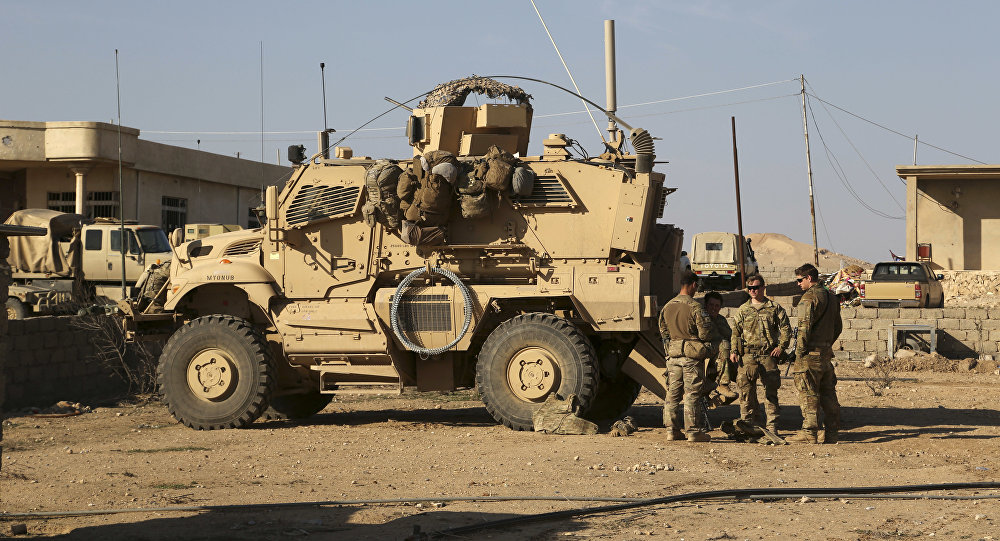 Feb. 23, 2017 photo, U.S. Army soldiers stand outside their armored vehicle on a joint base with Iraqi army south of Mosul, Iraq