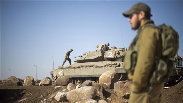 Israeli soldiers gather next to their tanks near the Syrian border in the occupied Golan Heights, November 28, 2016. (Photo by AP)