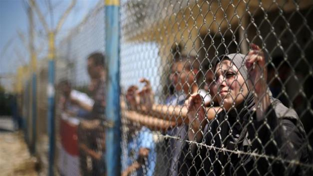 Palestinians gather in front of the gate of Rafah border crossing between Egypt and Gaza during a protest against the blockade calling for reopening of the crossing [Ibraheem Abu Mustafa/Reuters]