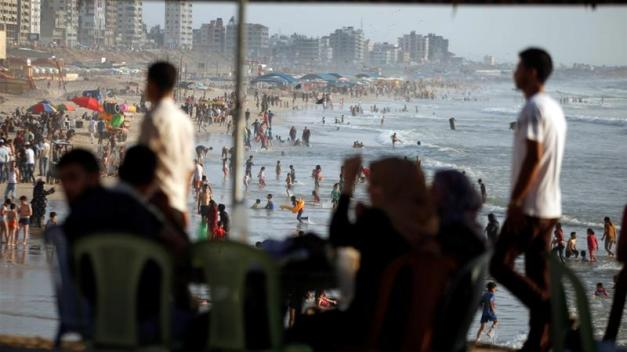 Palestinians spend time on a beach in a warm weather in Gaza City [Reuters]