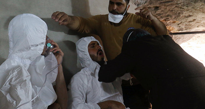 A man breathes through an oxygen mask as another one receives treatments, after what rescue workers described as a suspected gas attack in the town of Khan Sheikhoun in rebel-held Idlib, Syria