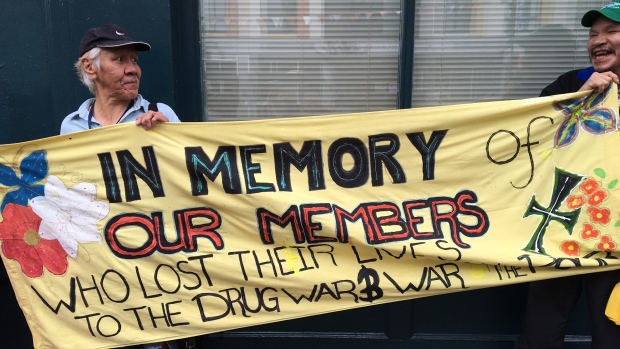 Two men hold up a sign at a June 8, 2016 rally in Vancouver calling for more supervised injection services to deal with a growing crisis of opioid-related overdose deaths.