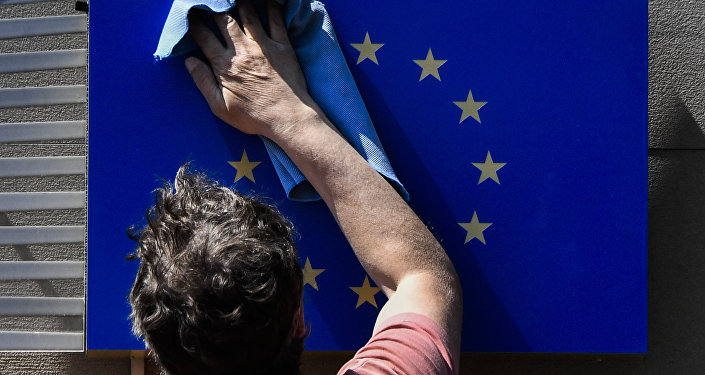 A worker wipes an EU flag clean.