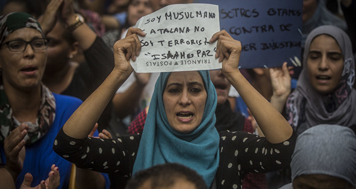 A woman holds a banner reading in Spanish: I am Muslim and Catalan, not a terrorist. Islam is Peace, during a protest by the Muslim community to condemn the vehicle attacks, in Barcelona, Spain