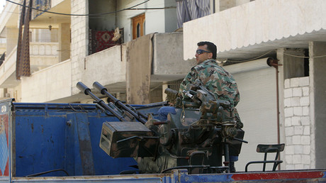 FILE PHOTO: A Free Syrian Army fighter sits on a pick-up truck mounted with anti-aircraft weapon © Muzaffar Salman
