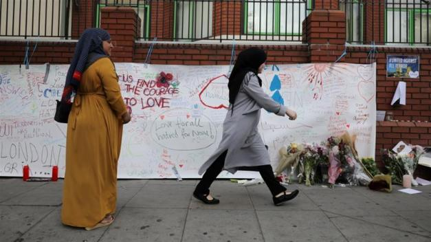 A woman walks past messages attached to a wall near the scene of an attack next to Finsbury Park Mosque, in north London Britain June 20, 2017 [Marko Djurica/Reuters]