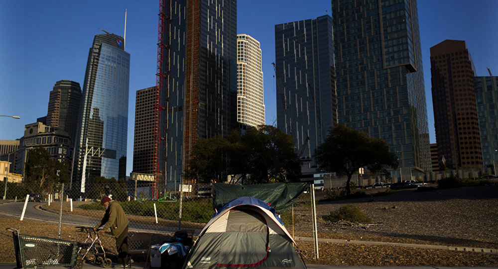 A homeless man, who declined to give his name, is dwarfed by skyscrapers Monday, Dec. 4, 2017, in Los Angeles. The U.S. Department on Housing and Urban Development release of the 2017 homeless numbers are expected to show a dramatic increase in the number of people lacking shelter along the West Coast.