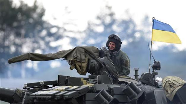 A Ukrainian soldier sits on a T-64BM tank prior the friendship shooting of several nations during the exercise Strong Europe Tank Challenge 2017, at the exercise area in Grafenwoehr, near Eschenbach, in southern Germany, on May 12, 2017. (Photo by AFP)