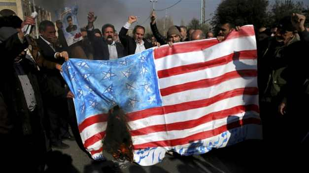 Iranians chant slogans as they burn a representation of the US flag in Tehran on Friday [Ebrahim Noroozi/AP]