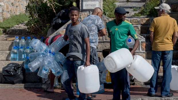 People queue to collect water from a natural spring outlet in the Cape Town suburb of St. James on Jan. 20. Residents are being advised to reduce daily water usage by over 40 per cent to avoid a Day Zero scenario that could happen in the coming weeks.