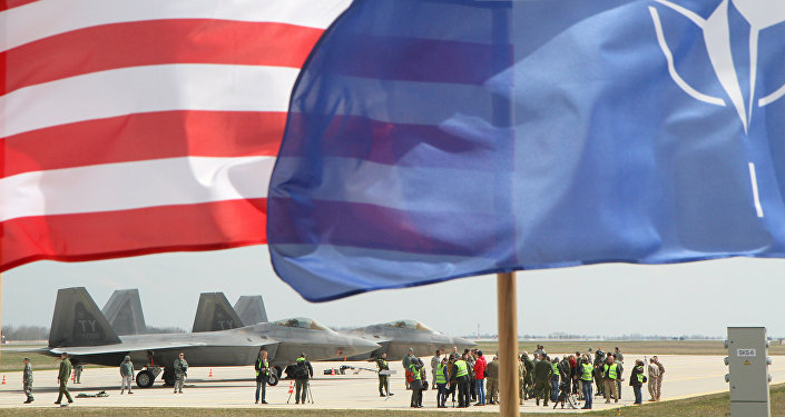 The US and The NATO flag flie in front of two US Air Force F-22 Raptor fighter aircrafts at the Air Base of the Lithuanian Armed Forces in Šiauliai, Lithuania.