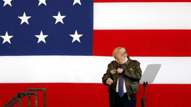 US President Donald Trump points to a detail on his flight jacket while on stage at US Air Force Yokota Air Base in Fussa, Japan [Toru Hanai/Reuters]